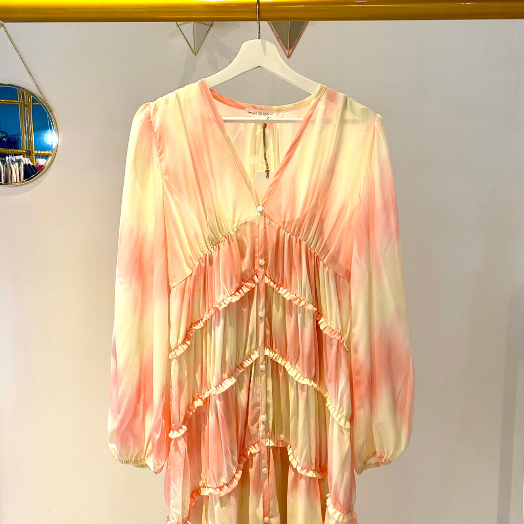 UNIKONCEPT: Lifestyle boutique; image shows a pale yellow and coral pink tie dyed dress by Free the roses. The Harlow tie dye dress features small ruffles from the chest to the mid calf. It has vertical buttons down the centre of the dress, puffy sleeves and is a high low style. The inside of the the dress comes with a nude slip to ensure it its not see through.