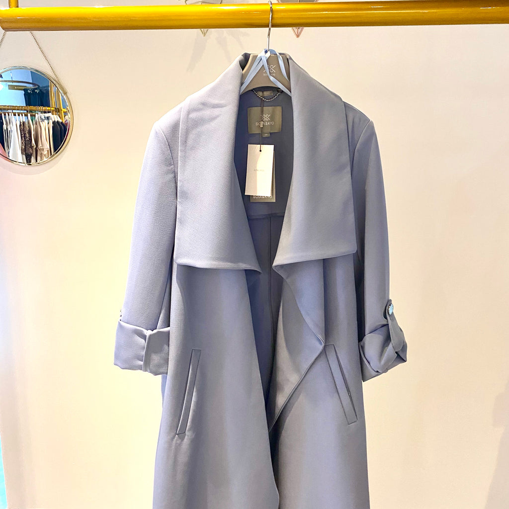 UNIKONCEPT: Lifestyle boutique; image shows a black trench coat by son and kyo. The Ornella coat in cerulean features pre rolled sleeves fashioned with silver buttons, a large collar and a stretchy belt matching the fabric and colour of the trench. It is mid length and can be worn multiple ways.