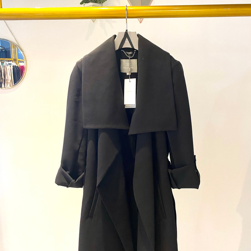 UNIKONCEPT: Lifestyle boutique; image shows a black trench coat by son and kyo. The Ornella coat in black features pre rolled sleeves fashioned with silver buttons, a large collar and a stretchy belt matching the fabric and colour of the trench. It is mid length and can be worn multiple ways.