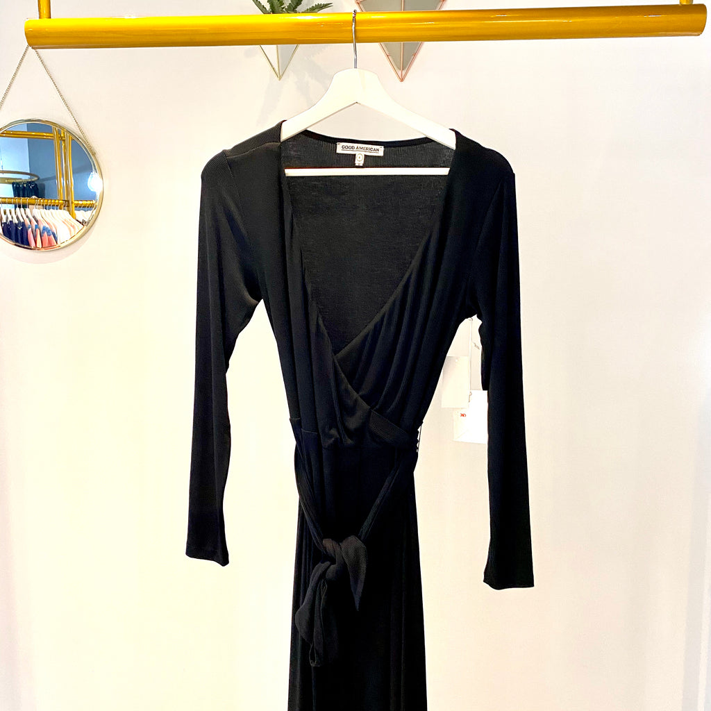 UNIKONCEPT Lifestyle boutique: image shows the Run Around Wrap Dress in black by Good American. This long-sleeve, ultra low v-neck, midi length, wrap dress is unbelievably soft and features the most flattering silhouette. The wrap detail cinches your waist perfectly and can be tied wherever you prefer the bow detail to sit. The fabric crosses of in the front allowing for a slit detail to run up the thigh.