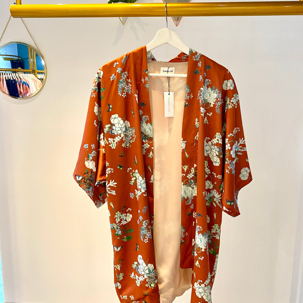 UNIKONCEPT Lifestyle boutique: Image shows the Maida Kimono Jacket by SugarLips. This relaxed, short kimono style jacket comes in a burnt orange with a white floral print.