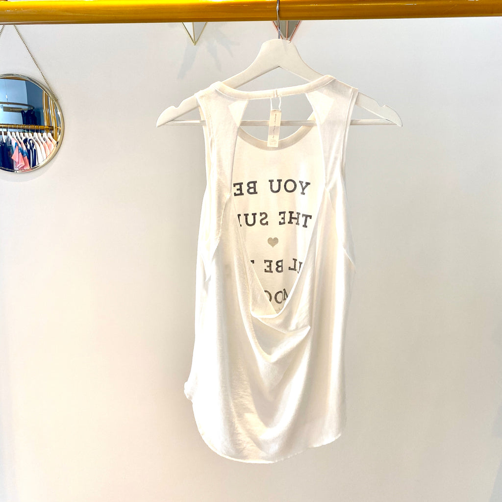 UNIKONCEPT Lifestyle boutique: image shows the Sun Studio Tank by Spiritual Gangster. This white scoop neck tank features an open back and print on the front that says 'You be the sun I'll be the moon' in black lettering.