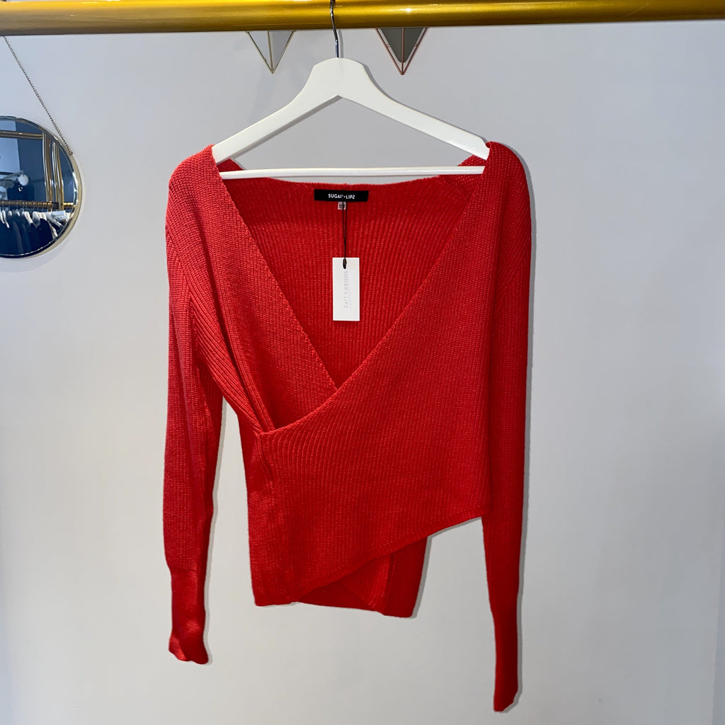UNIKONCEPT: Lifestyle boutique; Image shows a wrap sweater by sugar lips. The Britt wrap sweater is a thick bright red knit that features full long sleeves with a subtle pouffy arm length and a criss-crossed wrapped front section.