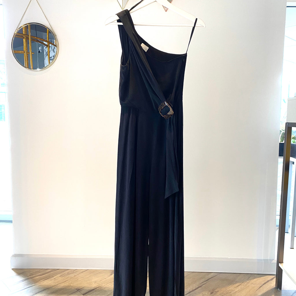 UNIKONCEPT Lifestyle boutique: Image shows the One Shoulder Jumpsuit in black by MinkPink. Thus one shoulder bodysuit features a fitted bodice and free flowing, full length pants. The waist of the jumpsuit features a tie detail with a brown clasp accent.
