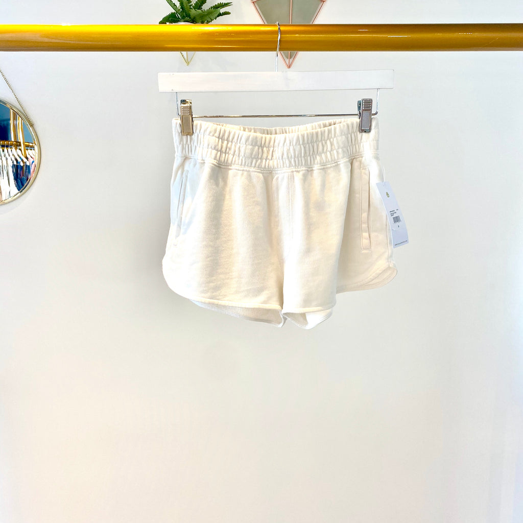 UNIKONCEPT: Lifestyle boutique: image shows a pair of white shorts by Spiritual Gangster. The zen mid rise shorts feature a ribbed elastic waistband and two pockets on either side of the hips.
