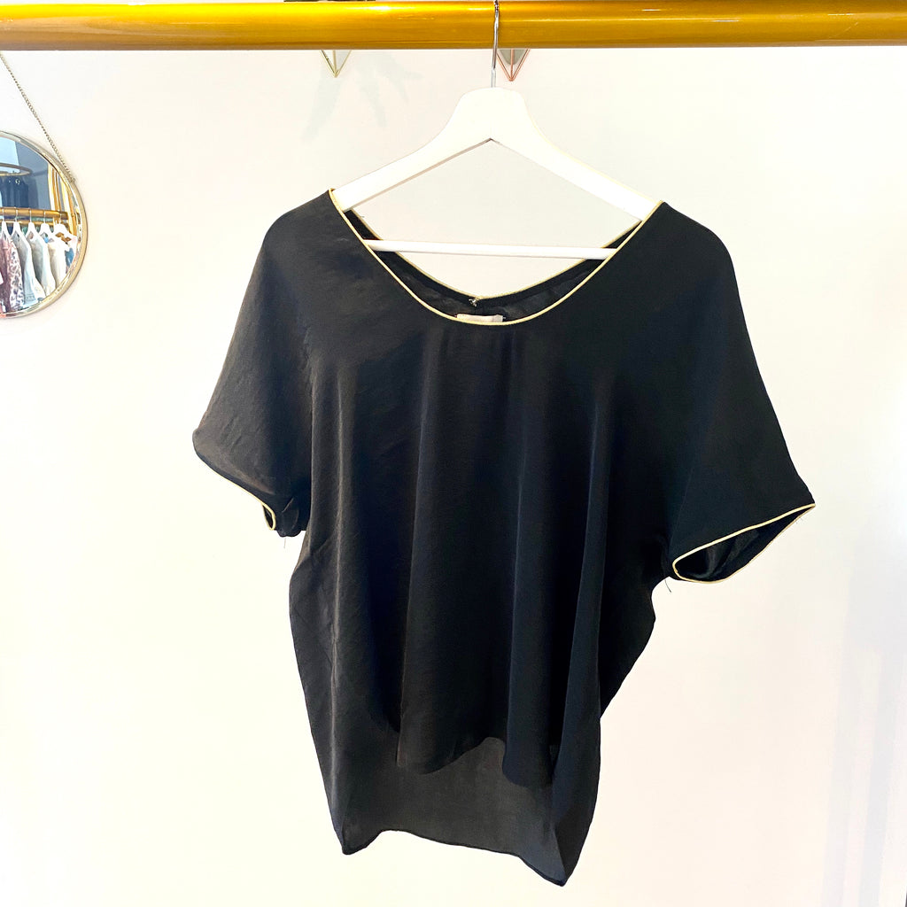 UNIKONCEPT Lifestyle boutique; image shows the Suzanne Tee in Black by Heartloom. This loose fitting black blouse features a round neckline. Both the neckline and sleeve hems are trimmed with a delicate gold.