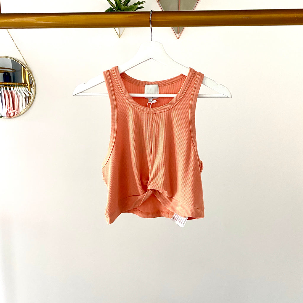 UNIKONCEPT Lifestyle boutique: This image shows the Twist Tank by MinkPink. This tank top features a high round neck, a ribbed fabric and is coral in colour. It is cropped with a twist detail in the front centre of the shirt.