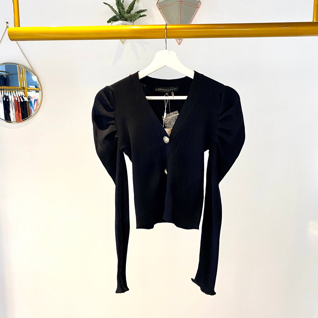 UNIKONCEPT Lifestyle boutique: the image shows the Sharp Shoulders Cardigan by Endless Rose. This long-sleeve, fitted, pant length cardigan is black and features three golden accent buttons down the front which also act as a closure. The shoulders feature a pleated puff detail that extends down the arm slightly.