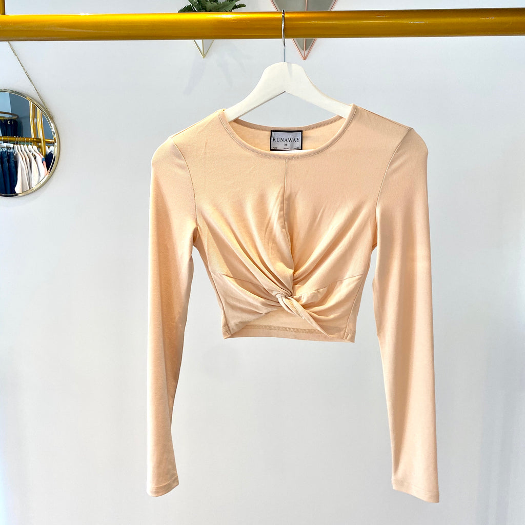 UNIKONCEPT Lifestyle boutique; image shows the Tina Top in a nude sand colour by Runaway. This cropped long sleeve tee is fitted and features a twist knot detail in the centre of the front hem of the shirt.