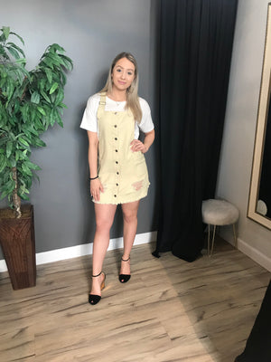 Model wears an overall styled Minkpink dress. The seeker distressed pinnie is a light wash natural/tan colour with distressed rips along the upper thigh. This outfit also features multiple buttons along the middle of the dress