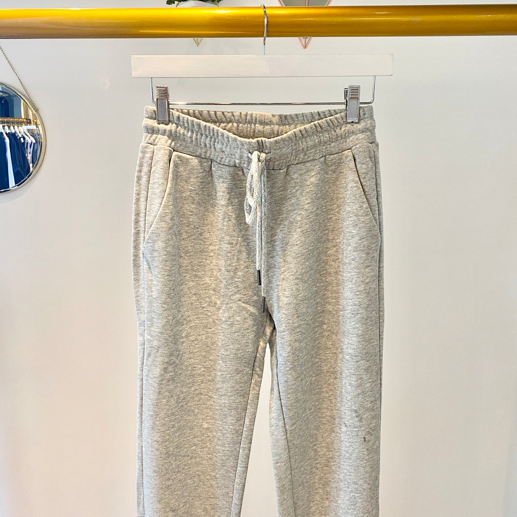 UNIKONCEPT Lifestyle boutique; image shows the Narella Jogger in grey by Heartloom. This jogger features an elasticized drawstring waistband, pockets and a tailored fitting leg. The pant leg hem is adorned by vertically placed button closures.