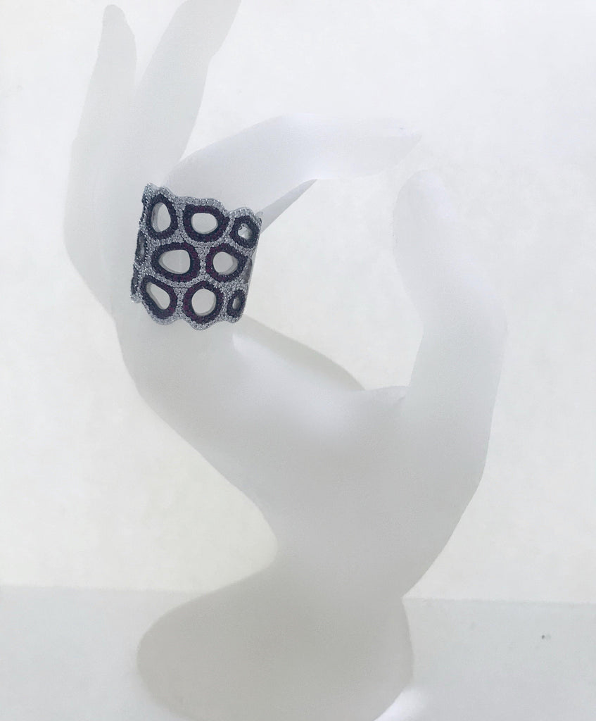 UNIKONCEPT Lifestyle boutique: Image shows the Georgina Ring by Adamar. This ring is a thick band which assumes a honeycomb pattern. It is made of silver and covered in blue and silver swarovski crystals which form a pattern that outlines the shape of the ring.