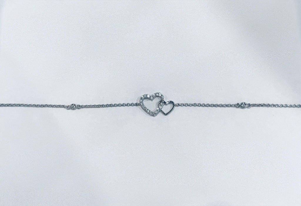 UNIKONCEPT Lifestyle boutique; image shows the Heart to Heart bracelet by Adamar. This bracelet features a dainty silver chain adorned with swarovski crystals which links to a silver double linked heart pendant. These two hearts are linked together, one being made of a thin silver and the other being thicker, and covered entirely in crystals.