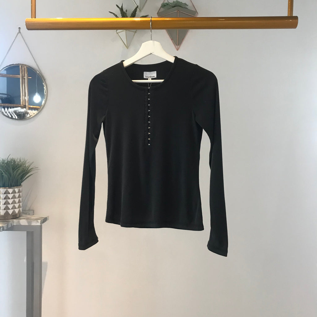 UNIKONCEPT Lifestyle boutique: Image shows a long black sleeve ribbed Heartloom top. The Rene Henley long sleeve in black is a perfect basic for every season, it features a ribbed material throughout and hook and eye closures from the mid chest to the top of the scoop neckline.