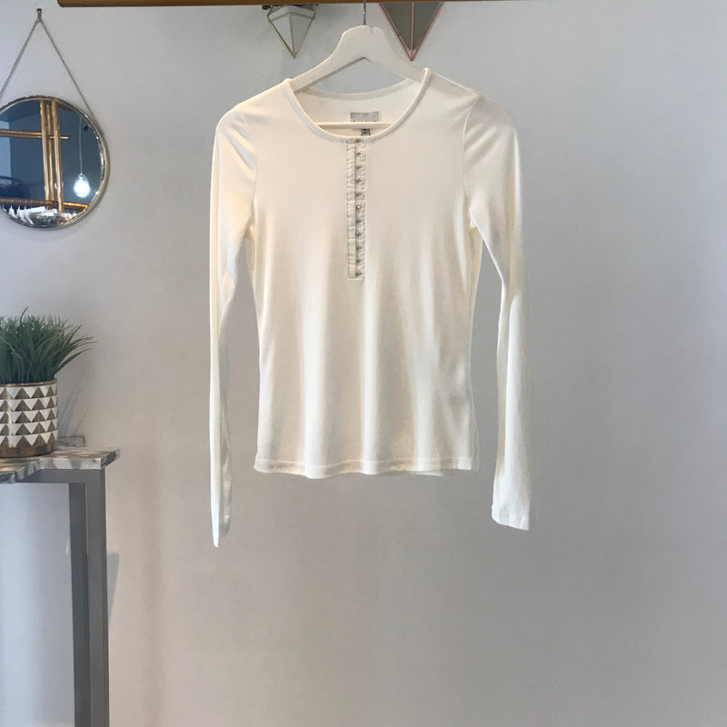 UNIKONCEPT Lifestyle boutique: Image shows a long white sleeved ribbed Heartloom top. The Rene Henley long sleeve in white is a perfect basic for every season, it features a ribbed material throughout and hook and eye closures from the mid chest to the top of the scoop neckline.