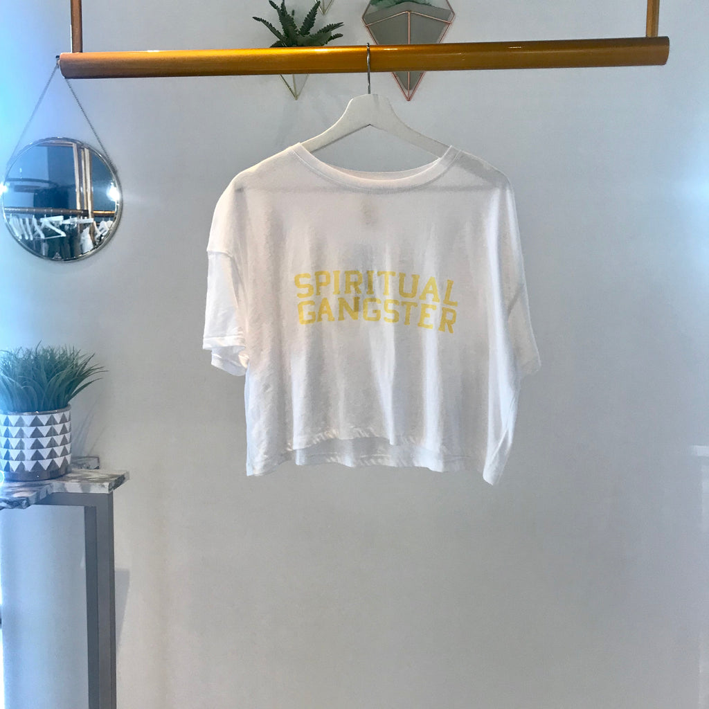 UNIKONCEPT Lifestyle boutique: image shows the Vera Cruz Crop Tee in white by Spiritual Gangster. This relaxed fitting, cropped tee features a rounded neckline and the brands name printed on the front in a yellow font.