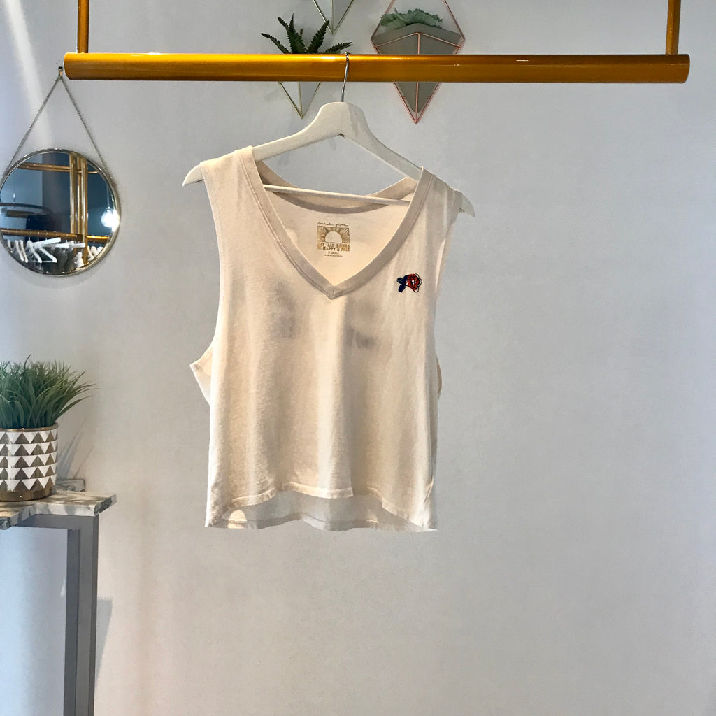 UNIKONCEPT Lifestyle boutique: image shows the Love is Deep N Neck by Spiritual Gangster. This white tank features a plunge v-neck with and embroidered flower on the front and 'Love is All We Need' with floral details on the back.