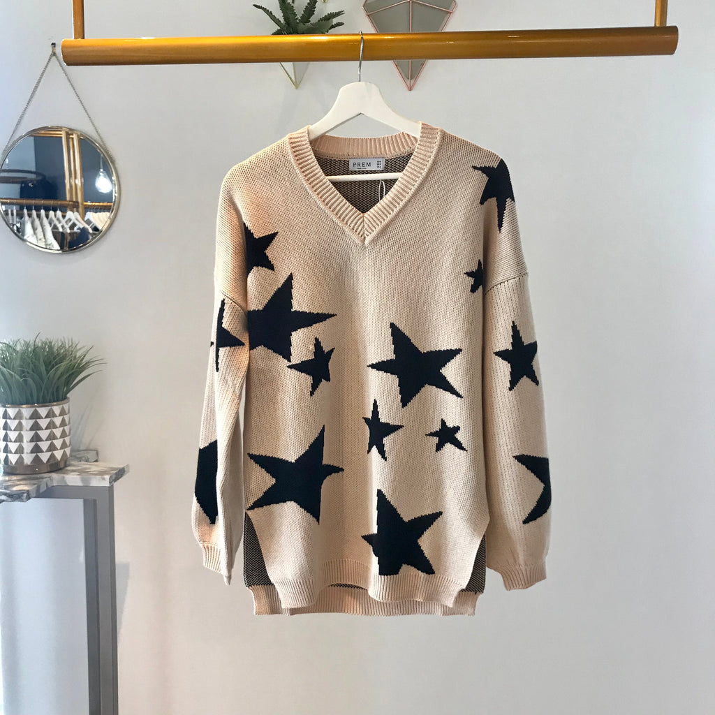 UNIKONCEPT Lifestyle boutique: Image shows a long sleeve oversized Runaway sweater. The shooting star knit is a nude based sweater with large and medium sized black stars all around. This sweater features puffy wide sleeved and a v neckline. The shooting star knit also has side slits on either side of the sweater.