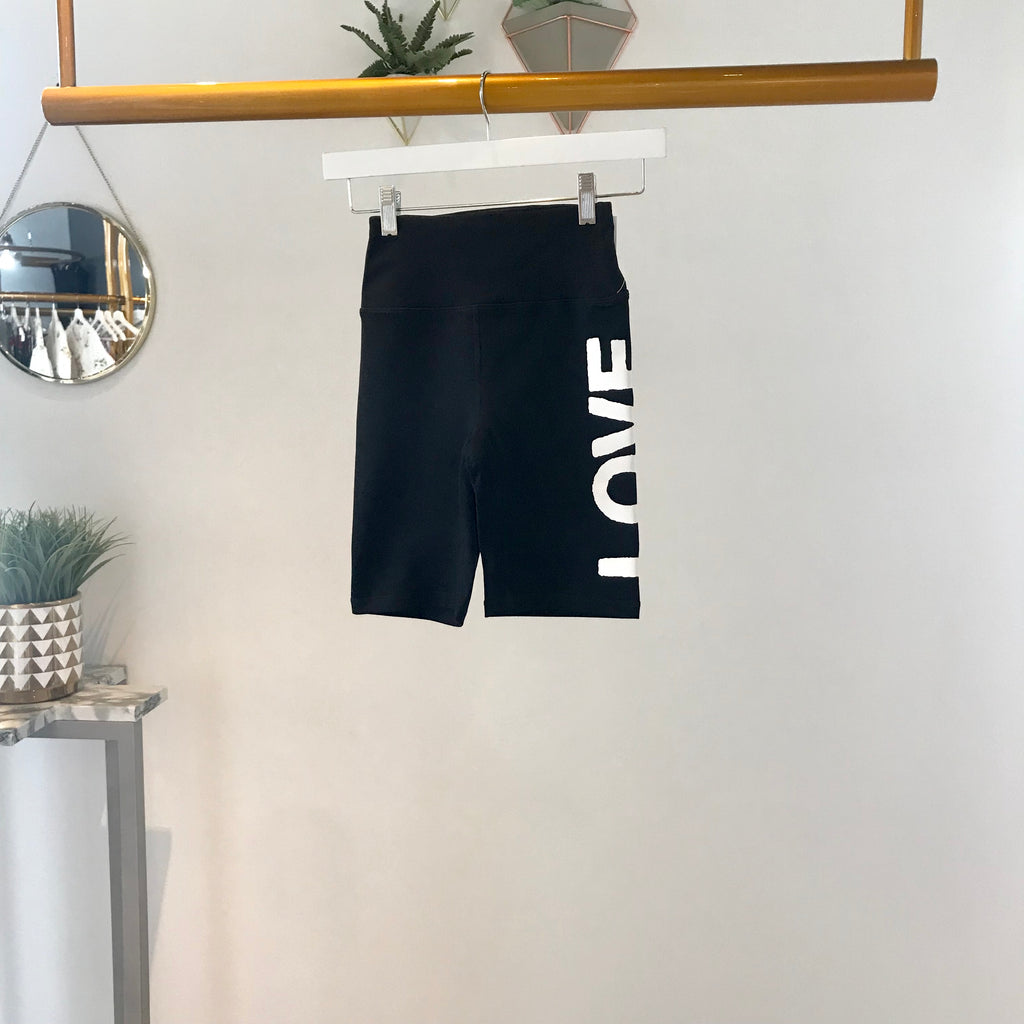 UNIKONCEPT Lifestyle boutique: Image shows the Love Gangster Bike Shorts by Spiritual Gangster. These highwaisted biker shorts are black and feature the word 'LOVE' written in white and all caps down the left leg