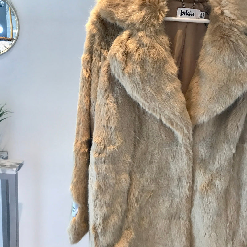 UNIKONCEPT: Lifestyle boutique; Image shows a faux fur coat by Jakke. The heather jacket is an oversized, hip length, tan coloured faux fur coat with a large collar. The heather coat features snap buttons starting at the chest and reaching down to the waistline.