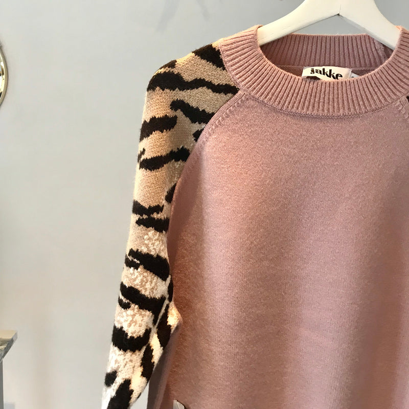 UNIKONCEPT: Lifestyle boutique; Image shows a faux wool sweater by UK brand, Jakke. The Sally sweater is light pink in colour and features a tiger print along the arms, shoulder to wrist in length. The sally sweater is a crewneck styled shirt with a scoop neckline and ribbed waistline.