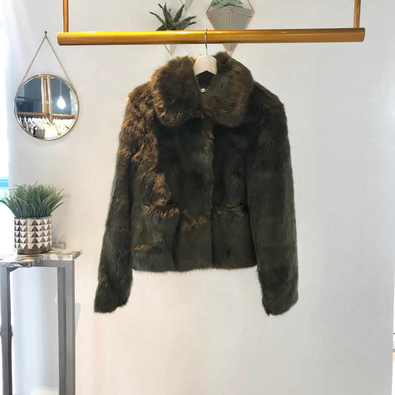 UNIKONCEPT: Lifestyle boutique; Images shows a faux fur Jakke coat. The Tommy jacket is an oversized cropped waist style. It is a khaki green colour and features snap down buttons from the neck to the waistline and a small colour around the neckline.