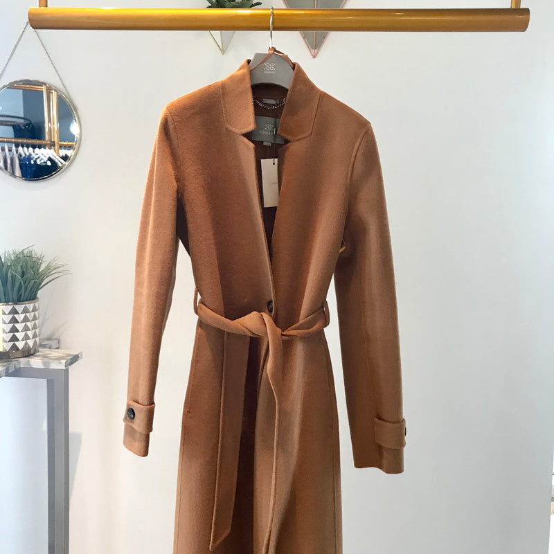 UNIKONCEPT Lifestyle boutique: Image shows a camel coloured long sleeve Soia & Kyo coat. The Ada Licia coat features a defined collar around the neck a centre button to close, a waist belt and buttons around the cuffs of the sleeves.