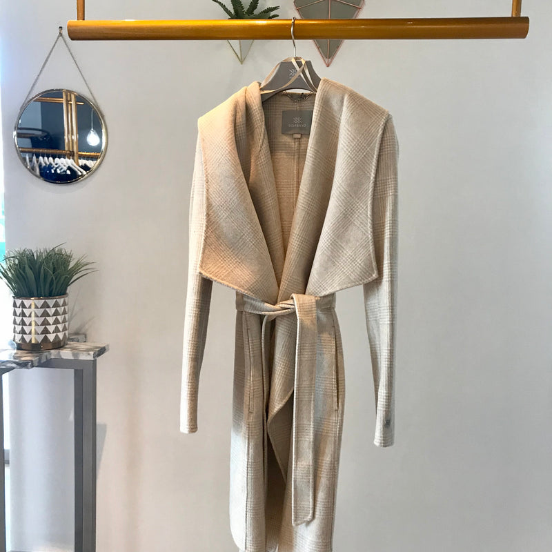 UNIKONCEPT: Lifestyle boutique; Image shows a Soia and Kyo waterfall formal jacket. The Samia coat in sandstone nude/neutral beige colour that features a cross hatched, plaid pattern throughout. It also features a wrap around belt that functions to tie and sinch in the waist, a large hood attached, waterfall inspired panels around the chest to mid thigh and a button on the left side of the body for closure.