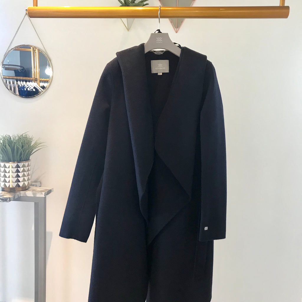 UNIKONCEPT: Lifestyle boutique; Image shows a Soia and Kyo waterfall formal jacket. The Samia coat in indigo is a indigo/navy colour, it features a wrap around belt that functions to tie and sinch in the waist, a large hood attached, waterfall inspired panels around the chest to mid thigh and a button on the left side of the body for closure.