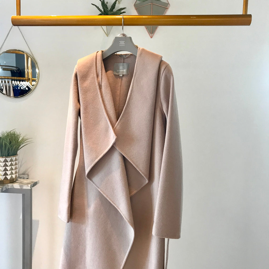UNIKONCEPT: Lifestyle boutique; Image shows a Soia and Kyo waterfall formal jacket. The Samia coat in rose quartz is a soft pink/nude colour, it features a wrap around belt that function to tie and pinch in the waist, a large hood attached, waterfall inspired panels around the chest to mid thigh and a button on the left side of the body for closure.