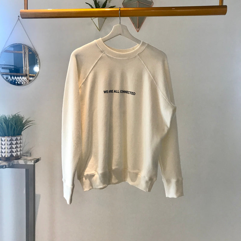 "UNIKONCEPT: Lifestyle boutique, The image shows a white crewneck by spiritual gangster. The connected crewneck feature full long sleeves and an elastic ribbed bottom. It has black printing the middle stating "" we are all connected"", the back features intricate and colourful deatiling of a circle with a triangle and daily affirmations around it."