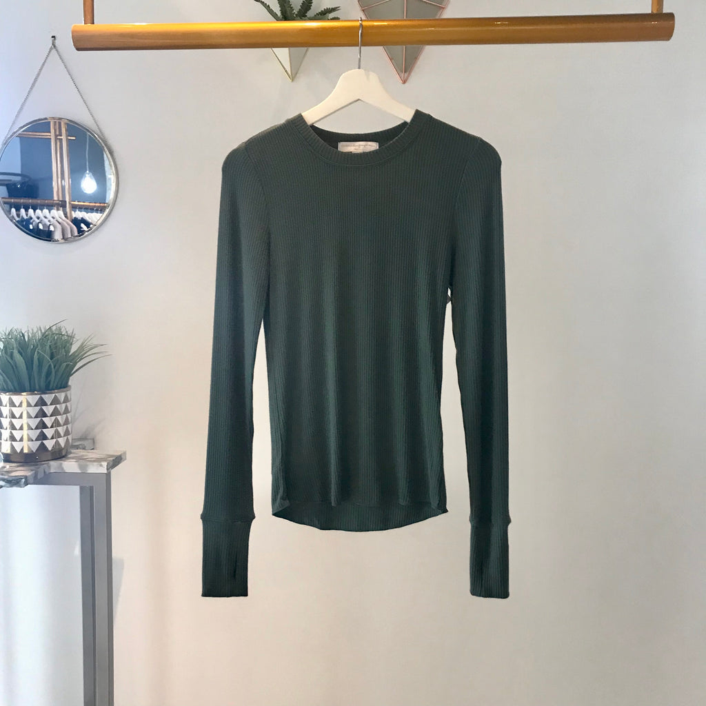 UNIKONCEPT: Lifestyle boutique; image shows a white long sleeve by spiritual gangster. The sanya crewneck is an olive green colour and features a ribbed material throughout a scoop neckline and finger holes at the bottom of the sleeves.
