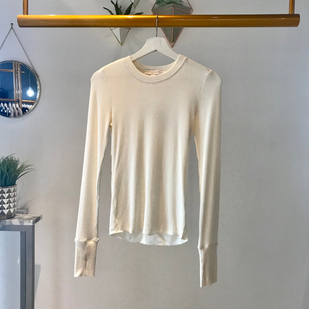 UNIKONCEPT: Lifestyle boutique; image shows a white long sleeve by spiritual gangster. The sanya crewneck is a stone white colour and features a ribbed material throughout a scoop neckline and finger holes at the bottom of the sleeves.