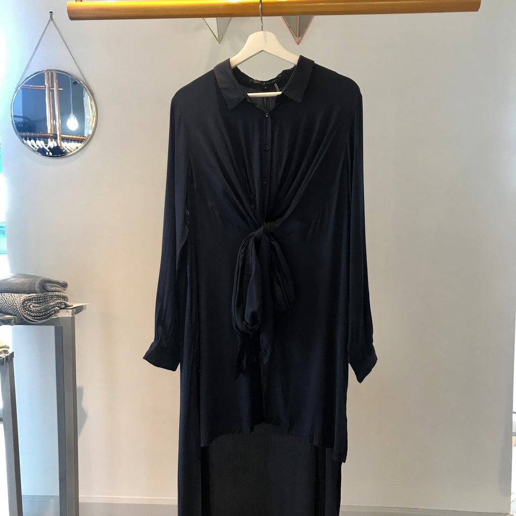 UNIKONCEPT:Lifestyle boutique - image shows a long sleeve duster blouse by English factory. The Ellie duster in navy is a long sleeve and button down top. It features long panels at the back and at the front with a bow in the middle of the stomach. It is a high low styled top with a shorter front showing minimal mid drift and a long back that cuts right after the knee/mid calf area.