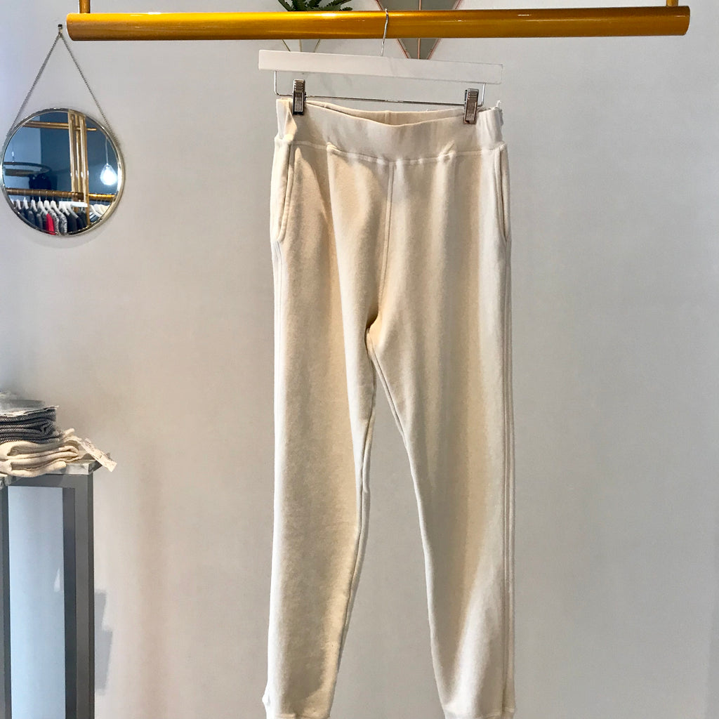 UNIKONCEPT: Lifestyle boutique image shows a pair of natural stone coloured joggers by sam and lavi. The Isabella pant features pockets and full length legs with distressed hemlines and ankle lengths.