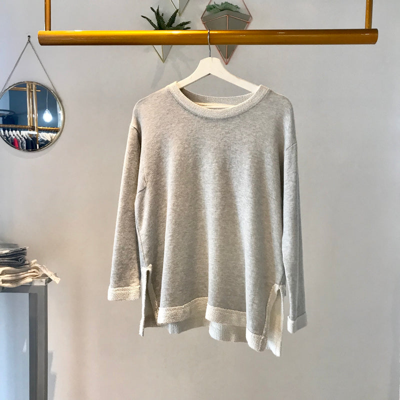 UNIKONCEPT: Lifestyle boutique; Image shows a ash pebble Terry crewneck with a distressed collar and sleeves. The piper top by sam and lavi features a distressed  whiter coloured hem detail around the wrists, the neckline and the bottom portion of the top. It is an oversized relaxed fit with a shorter front section and longer in the back