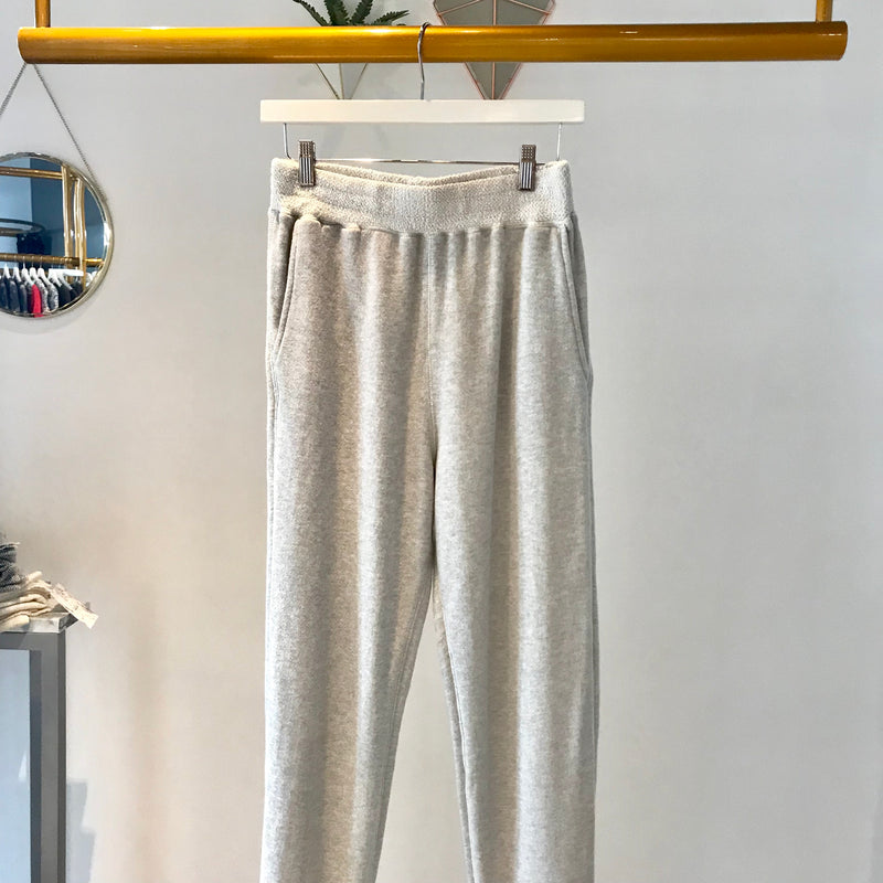 UNIKONCEPT; Lifestyle boutique - Image shows a pair of ash pebble Terry jogger pants by Sam and Lavi. The Brook pant has an unfinished/distressed waistline that is lighter than the rest of the pant. The pant is relaxed with a tight cuff on the bottom and features a raised hem on the front with a longer back portion making it perfect to wear with booties.