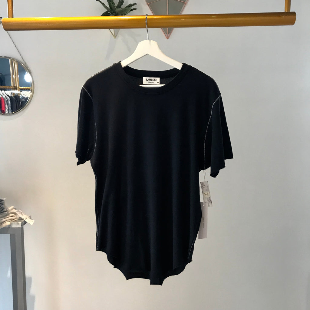 UNIKONCEPT: Lifestyle boutique; image shows a relaxed black tee by Sam and Lavi. The colette top is a boyfriend style tee with  white stitching around the hems, neckline, shoulders and sleeves. it features a scoop neckline and semi circle hem.