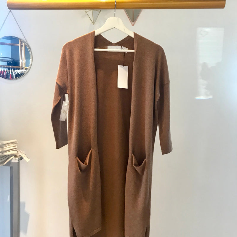 UNIKONCEPT: Lifestyle boutique; image shows a neutral, camel coloured Cardigan. The creme brûlée cardigan by Kersch is a 3/4 length opened cardigan with pockets.