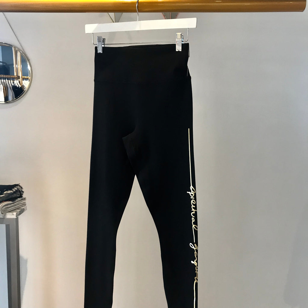 UNIKONCEPT Lifestyle boutique: image shows the essential HW leggings by Spiritual Gangster. These solid black highwaisted leggings feature small gold detailing on the left leg that states the brand name in an elegant cursive font.