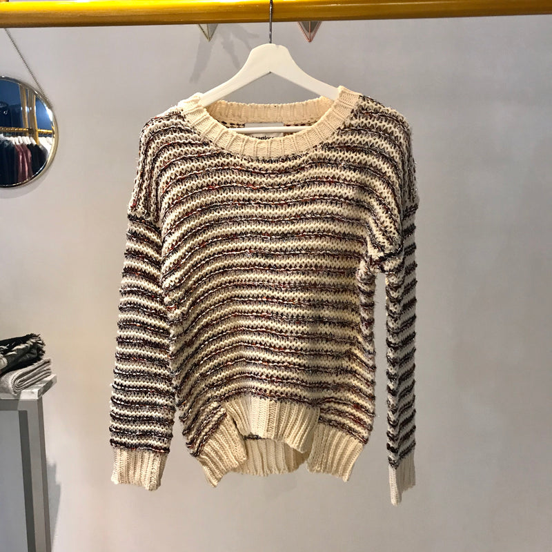 UNIKONCEPT: Lifestyle boutique; Image shows a horizontally ribbed holiday sweater by heart loom. The Beth sweater is a cream crewneck styled sweater that feature ribbed knit detailing throughout with small sparkly Burgundy and gold threads. It also features two front slits at the base/ hip area of the sweater.
