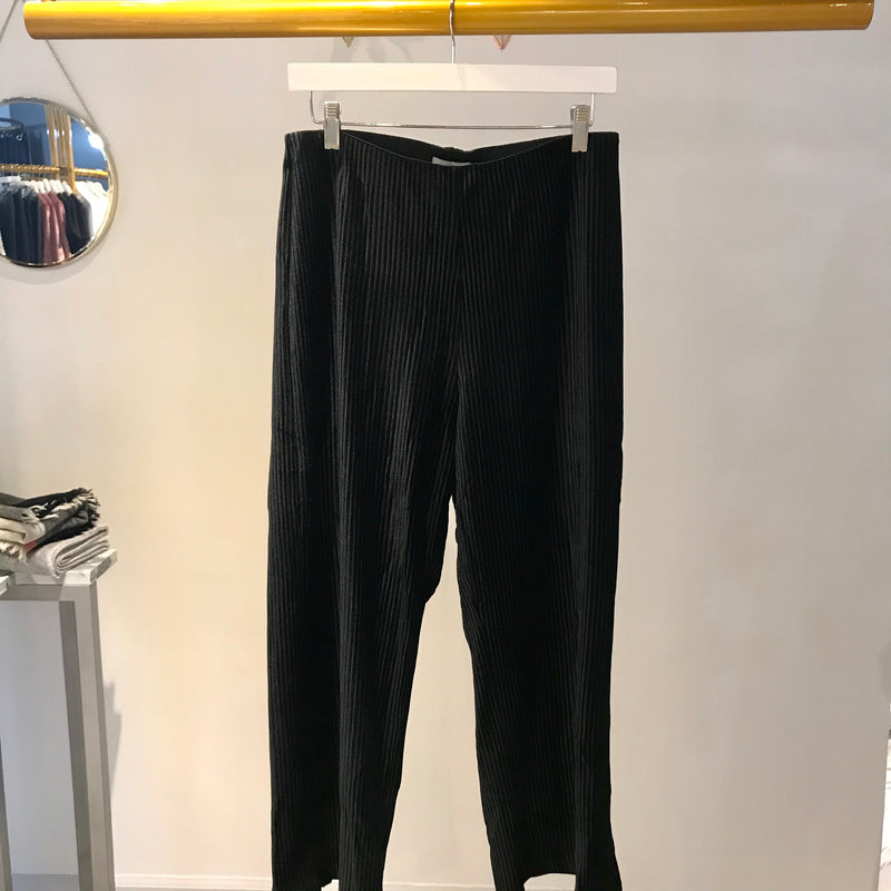 UNIKONCEPT: Lifestyle boutique; image shows a pair of black ribbed wide leg pants by heart loom. The drea pant are a formal culotte that feature an elastic waistband and a velvet feel throughout.