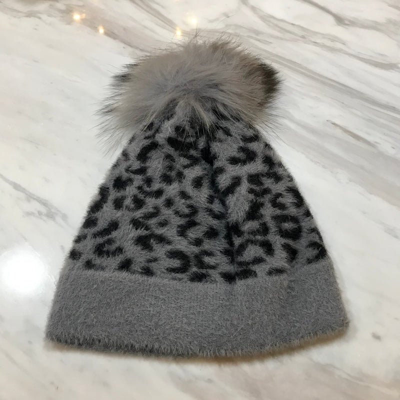 UNIKONCEPT: Lifestyle boutique; Image shows a grey leopard print hat by heart loom. The Fiona beanie features a grey coloured real fur pom at the top of the hat as well
