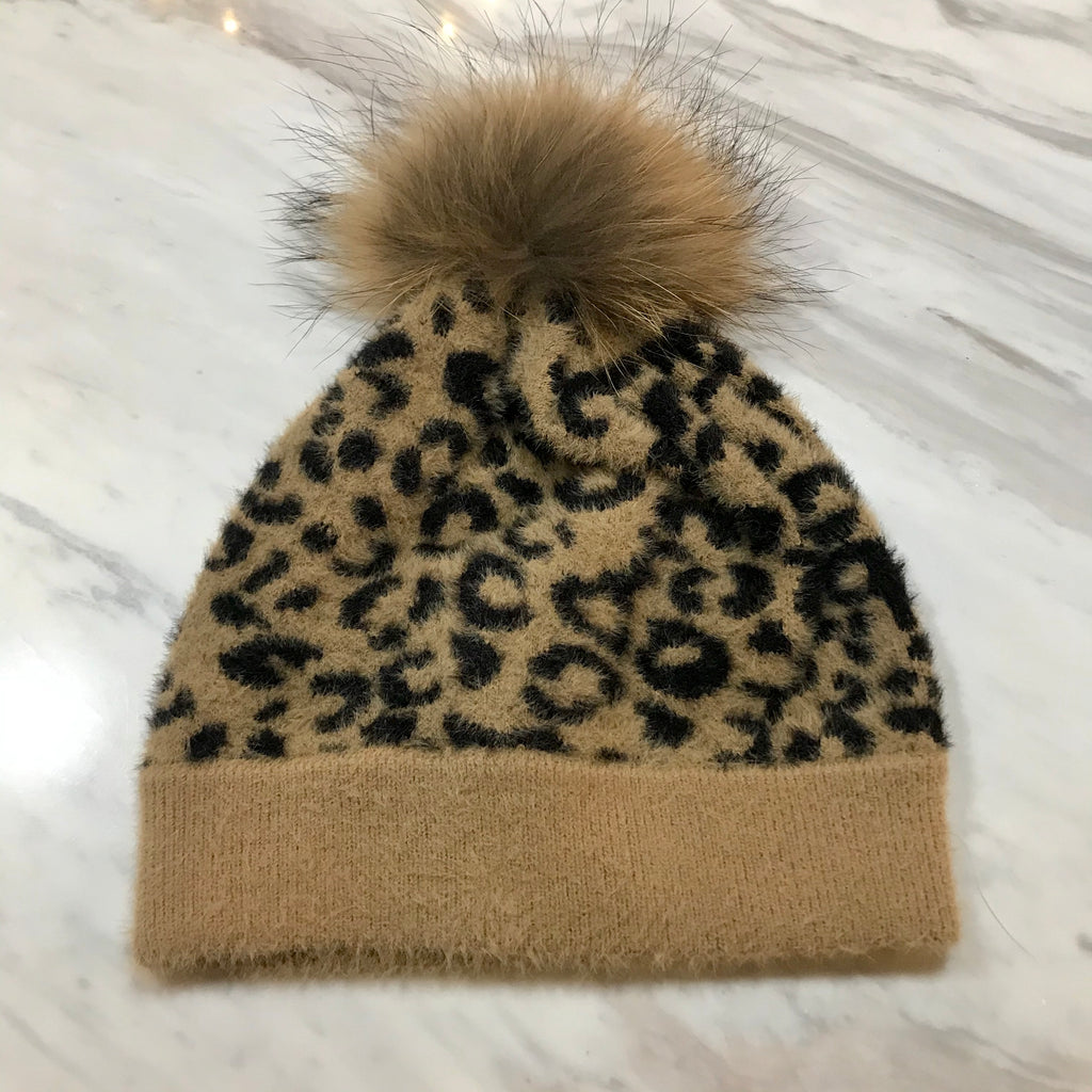 UNIKONCEPT: Lifestyle boutique; Image shows a leopard print hat by heart loom. The Fiona beanie features a tan coloured real fur pom at the top of the hat as well