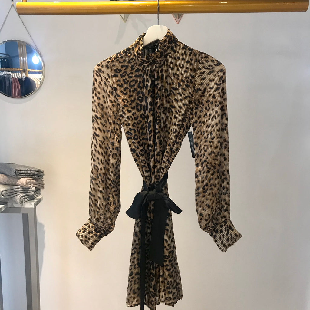 UNIKONCEPT: Lifestyle boutique; image shows a leopard print dress by sugar lips. The Anastasia dress feature a full leopard print long sleeve dress with a mock neck. It also features a black satin like ribbon that wraps around the waist.