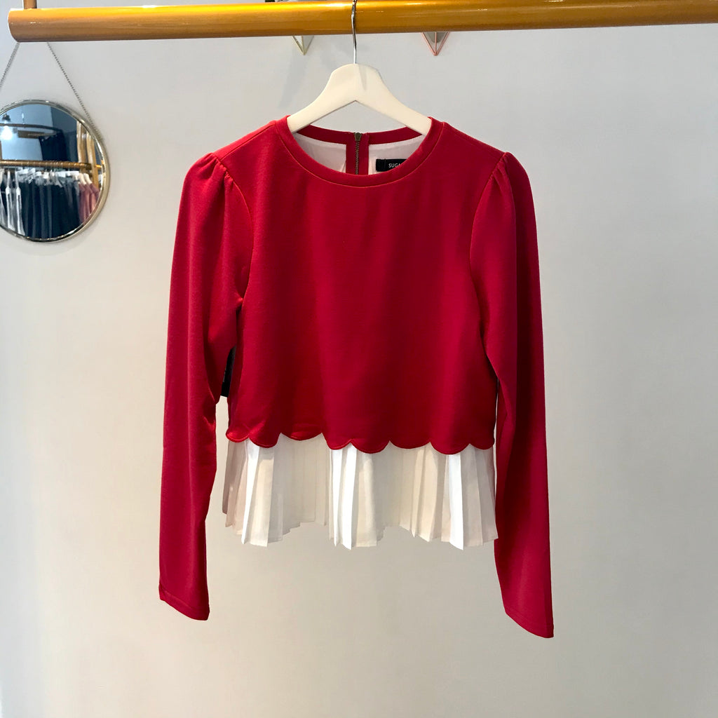 UNIKONCEPT: Lifestyle boutique; image shows a long sleeve sweater blouse by Sugar lips. The Gotta Have It sweater blouse is a bright cherry red cotton like long sleeve with a pleated white linen like underlay. This top also features a scalloped edge where the white fabric meets the red and a gold zipper at the back of the neck for easy access.