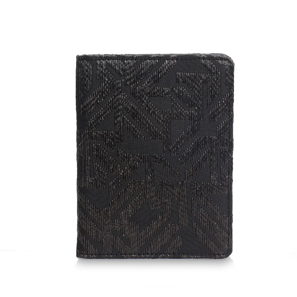 Image shows a pixie mood passport wallet. The jana passport wallet in black woven has aztec like woven pattern.