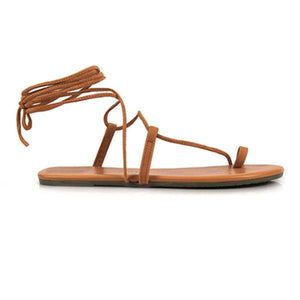 UNIKONCEPT lifestyle boutique: Image shows a pair of brown gladiator sandals by Tkees. The Tkees sandals are light brown in colour and feature a single strap across the toe, the middle of the foot and beside the ankle. The rest of the shoe is tied around the ankle with thin light brown strings.