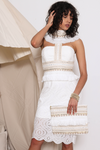 Model is wearing the Makeda Midi Dress from Prem. Bridal wear: Model wears an eccentric white midi dress with a high collared neckline with frills and Egyptian-like embellishments which carries on through the middle of the bust and hugs the waistline.