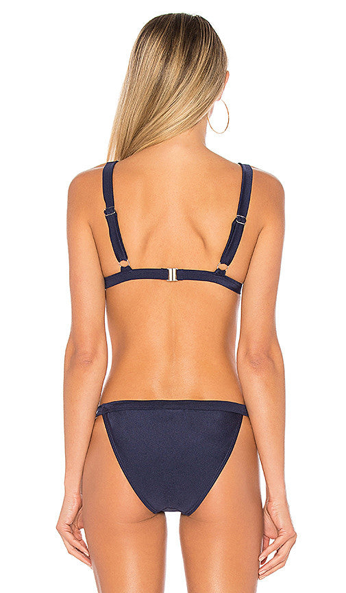 Model wearing navy triangle bikini top by Minkpink. The lucky star triangle bikini top in indigo features 1 inch wide straps and a plunge v-neckline.
